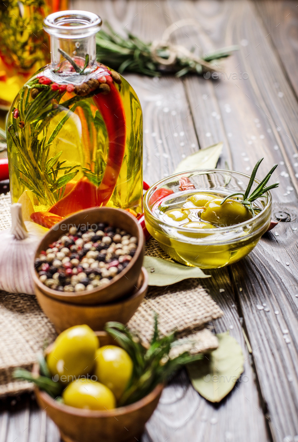 Green olives oils and spices on kitchen table. Cooking concept - Stock Photo - Images