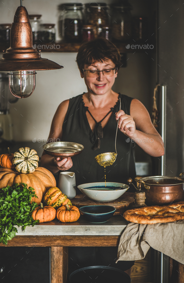 Elderly woman serving Autumn seasonal pumpkin cream soup - Stock Photo - Images