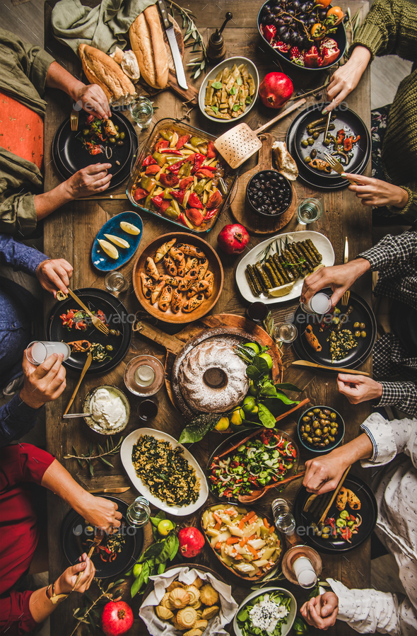 Turkish family feasting at table with traditional foods and raki - Stock Photo - Images