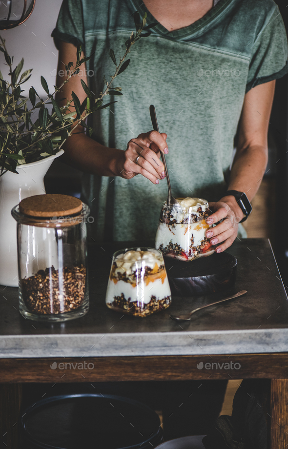 Woman having healthy breakfast with yogurt, granola and fruit - Stock Photo - Images