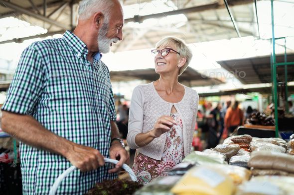 Senior family couple choosing bio food fruit and vegetable on the market during weekly shopping - Stock Photo - Images