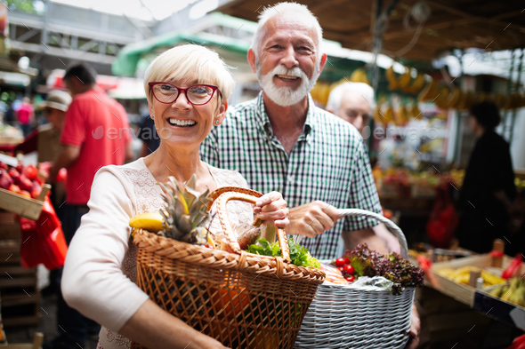 Mature couple shopping vegetables and fruits on the market. Healthy diet - Stock Photo - Images