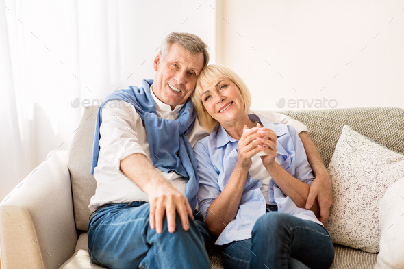 Happy mature couple sitting on sofa and embracing - Stock Photo - Images