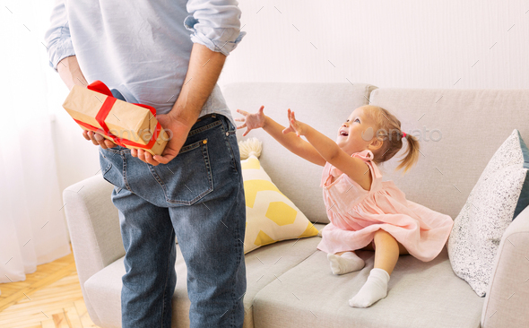 Adorable daughter wants to cuddle with father - Stock Photo - Images