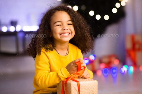 Happy african girl unwrapping her xmas gifts at home - Stock Photo - Images