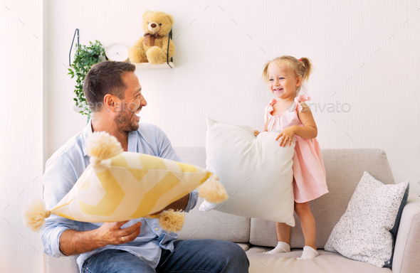 Playful family having a pillow fight together - Stock Photo - Images