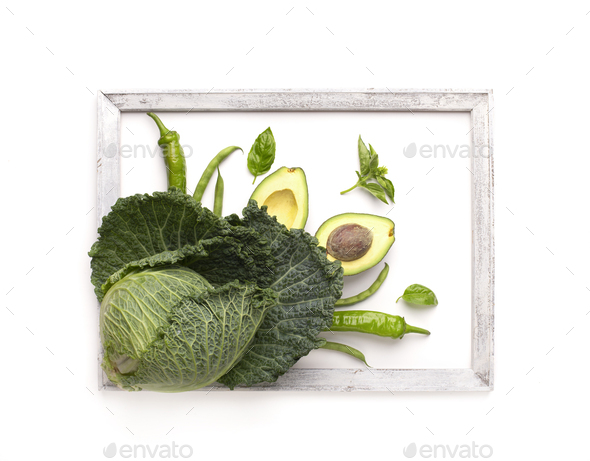 Green vegetables decorating white background and surrounded by wooden frame - Stock Photo - Images