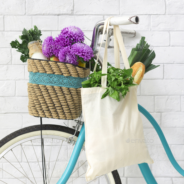 Eco friendly retro bike decorated by violet wildflowers and shopping bag - Stock Photo - Images