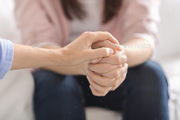 Close up of therapist touching woman patient hands - Stock Photo - Images