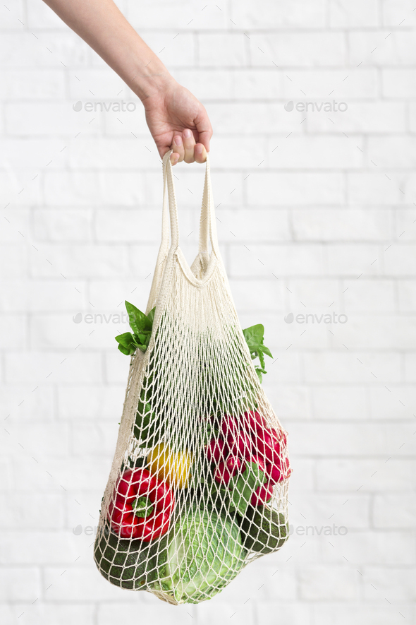 Eco cotton shopping bag with fresh and clean vegetables in woman hand - Stock Photo - Images