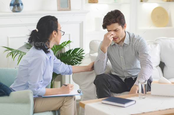 Depressed man feeling drawn at psychotherapist session - Stock Photo - Images