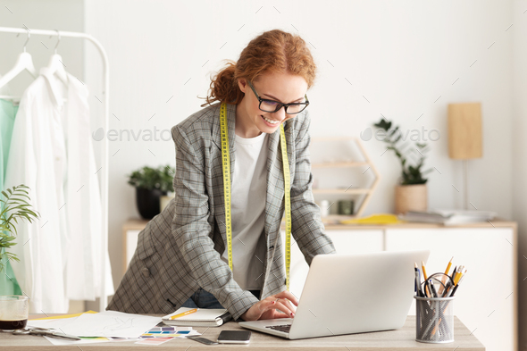 Confident tailor working on laptop in own dressmaking studio - Stock Photo - Images
