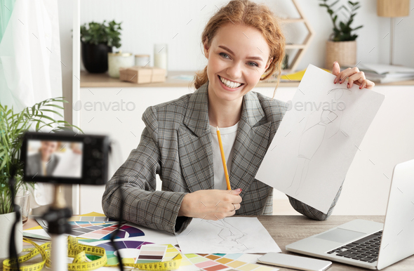 Fashion designer recording video for her blog, showing sketches - Stock Photo - Images