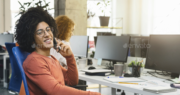 Positive black man having pleasant conversation in office - Stock Photo - Images