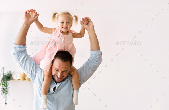 Cute girl riding on her father's shoulders - Stock Photo - Images