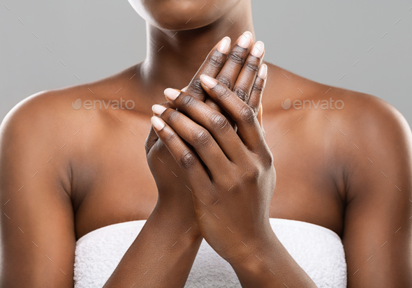Unrecognizable afro woman applying moisturizing cream to her hands - Stock Photo - Images