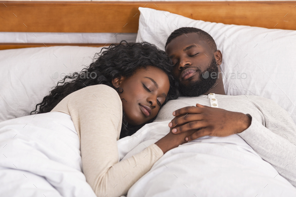 Afro couple sleeping in comfortable bed at home - Stock Photo - Images