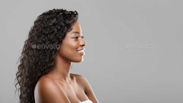 Beautiful black girl looking aside at copy space on gray background - Stock Photo - Images