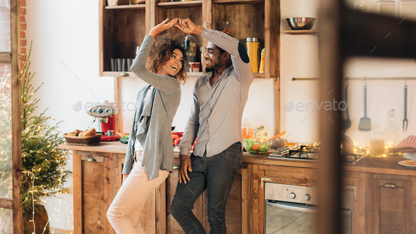 Young african-american couple dancing in kitchen, copy space - Stock Photo - Images