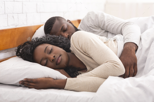 Afro couple sleeping together in comfortable bed at home - Stock Photo - Images