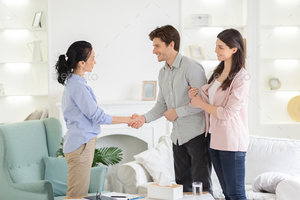 Psychologist and thankful couple handshaking in office - Stock Photo - Images