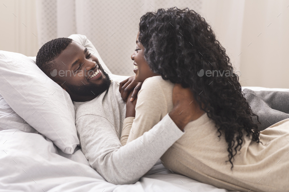 Smiling black couple having fun in bed, embracing and flirting - Stock Photo - Images