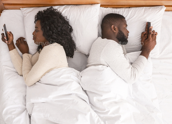 Afro couple using smartphones in bed, ignoring each other after quarrel - Stock Photo - Images
