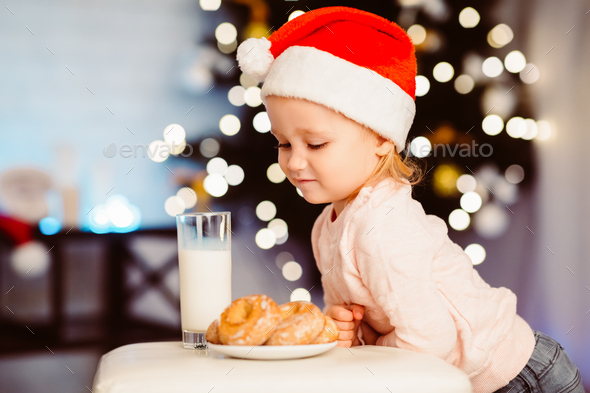 Cute little girl looking at treats for Santa near Christmas tree - Stock Photo - Images