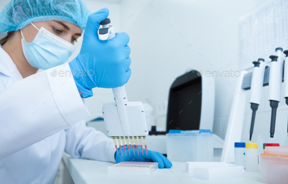 Woman collecting blood samples from pipette for testing - Stock Photo - Images