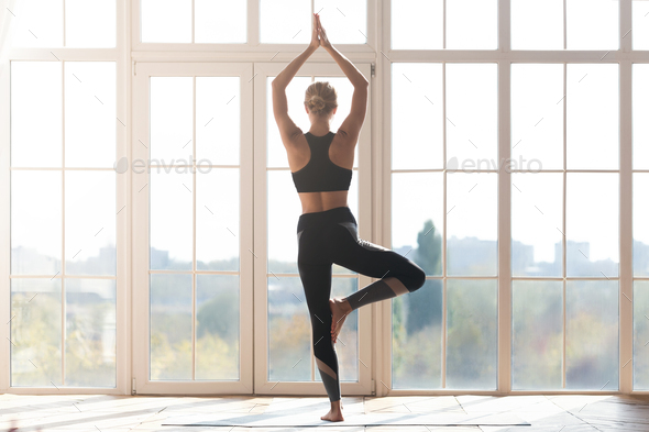 Young woman doing yoga at studio, tree pose - Stock Photo - Images