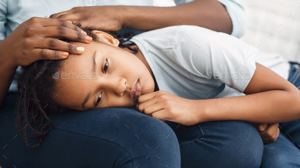 Close-up of black girl's head laying on lap - Stock Photo - Images