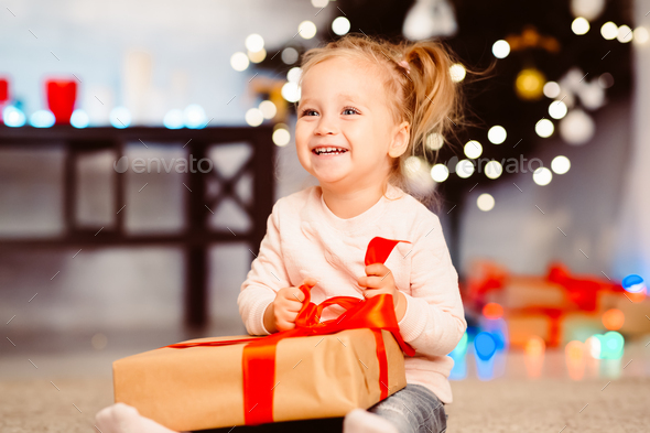Cute little girl opening Christmas gift at home - Stock Photo - Images