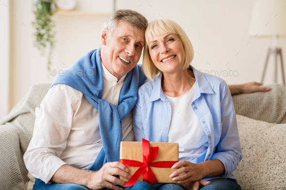 Happy senior spouses holding giftbox and smiling to camera - Stock Photo - Images