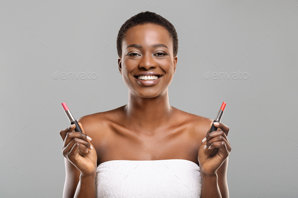 Black woman choosing between two lipstick colors, red and pink - Stock Photo - Images