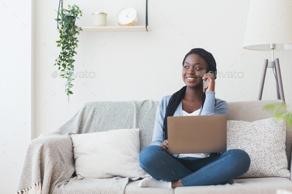Afro girl talking on cellphone and using laptop at home - Stock Photo - Images