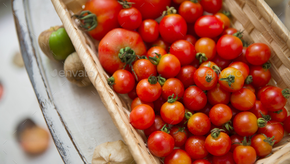 Organic and fresh tomatoes in eco wooden box on chair - Stock Photo - Images