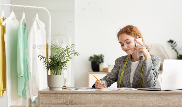 Young fashion designer discussing customer's order on phone - Stock Photo - Images