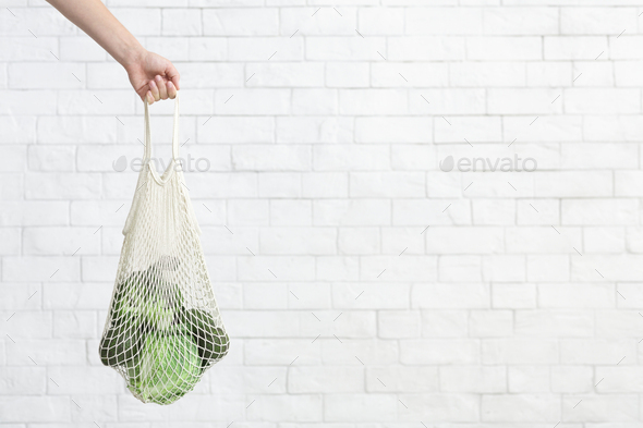 Eco and fresh green vegetables collecting inside mesh shopping bag - Stock Photo - Images