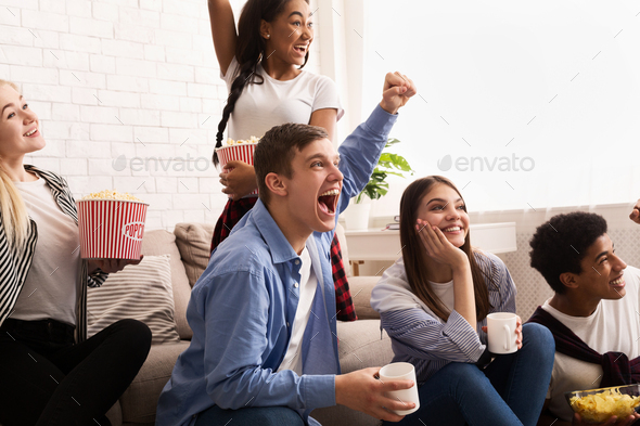 Emotional teenagers watching football on tv and cheering - Stock Photo - Images