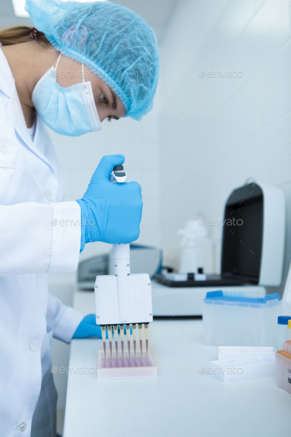 Young female scientist drops red samples in test tubes - Stock Photo - Images