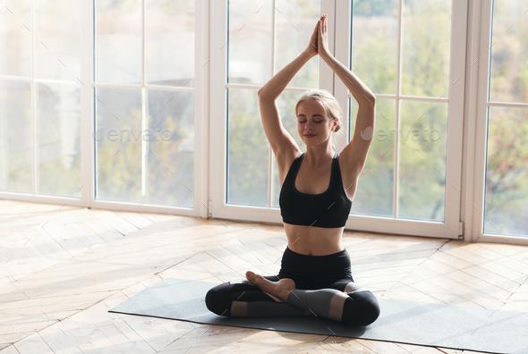 Peaceful girl having morning yoga practice at studio - Stock Photo - Images