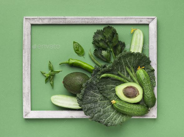 Composition of fresh green vegetables inside wooden frame - Stock Photo - Images