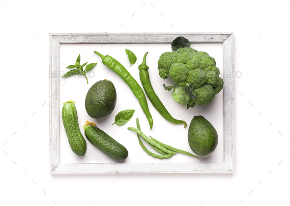 Creative picture of green vegetables inside wooden frame - Stock Photo - Images