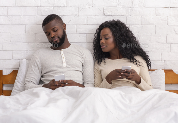 Jealous man peeking into wife's cellphone sitting on bed together - Stock Photo - Images