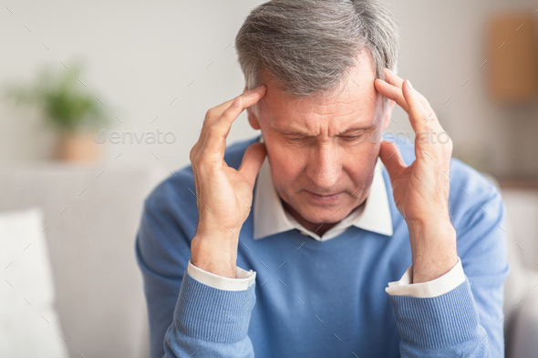 Senior Man Suffering From Migraine Sitting On Sofa At Home - Stock Photo - Images