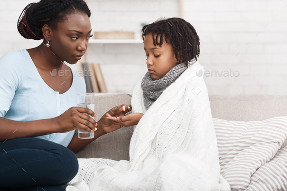 Black mom giving medicine for flu to child - Stock Photo - Images