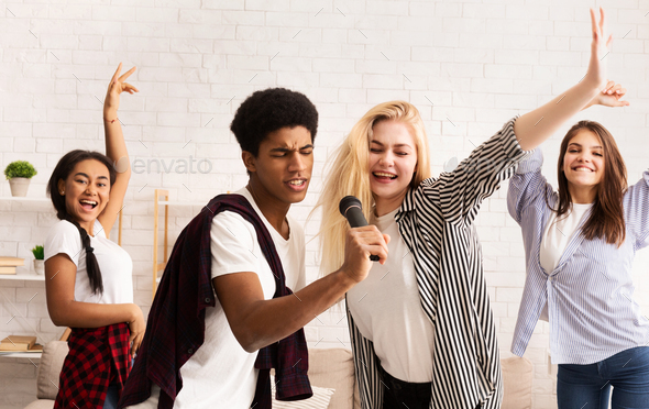 Teen friends having party and singing karaoke - Stock Photo - Images