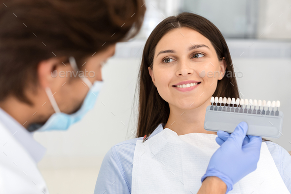 Dentist putting sample from tooth scale to smiling woman - Stock Photo - Images