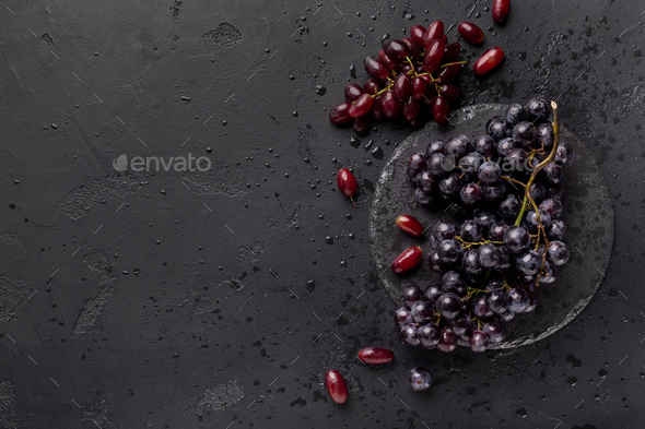 Healthy flat lay of colored grape on black background - Stock Photo - Images