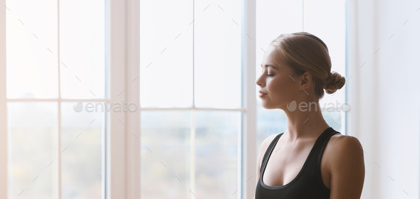 Portrait of harmonious young girl with closed eyes against window - Stock Photo - Images